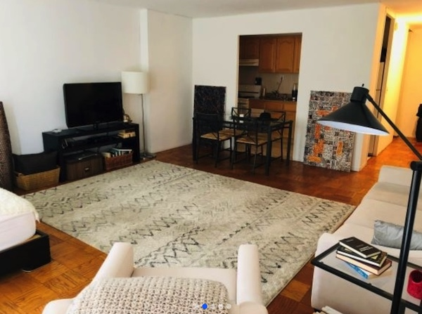apartment listing photo of living room with coffee table, tv, rug.