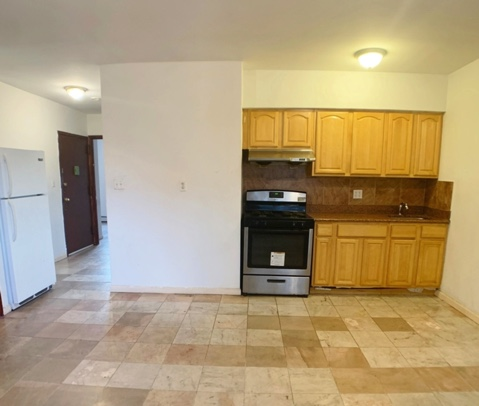 apartment listing photo of empty kitchen space with fridge