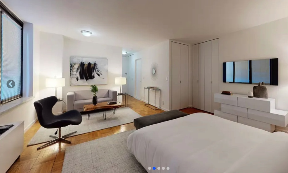 photo of studio apartment with bed and rest of the space in frame