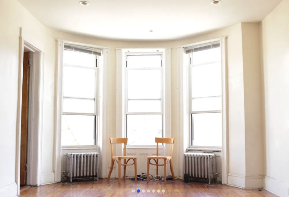 apartment photo of big windows and two chairs