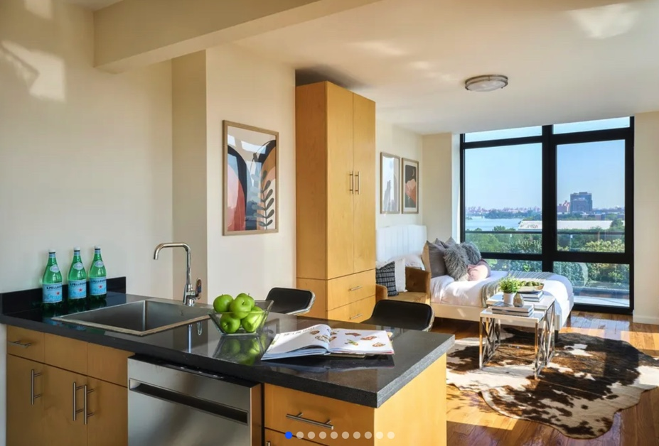 apartment listing photo of furnished studio bedroom with bed, kitchen table, and view of outdoors
