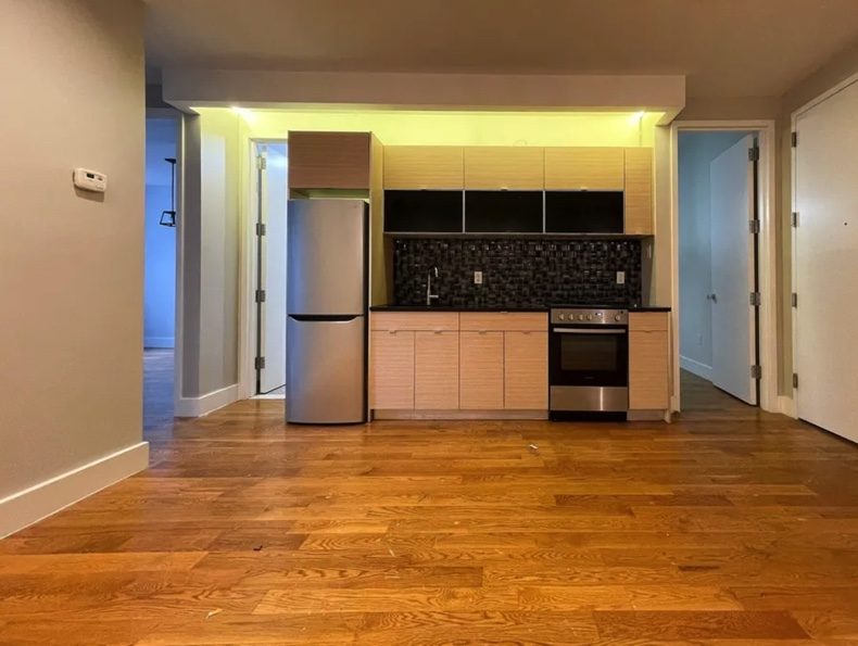 apartment listing photo of kitchen and empty living room