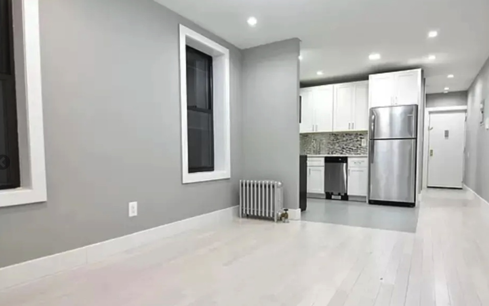 apartment listing photo empty living room, kitchen, and foyer with front entrance